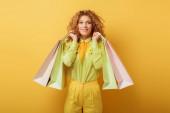 šťastná zrzka žena drží nákupní tašky na žluté