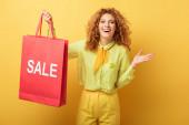 veselý ryšavý žena drží nákupní taška s prodejem nápisy na žluté
