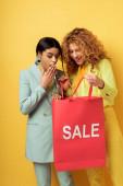 boldog vörös lány gazdaság bevásárló táska eladó betűkkel közel meglepett afro-amerikai nő elszigetelt sárga