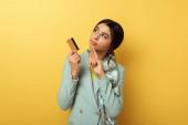 nachdenkliches afrikanisch-amerikanisches Mädchen mit Kreditkarte und Zeigefinger auf gelb