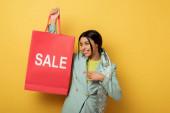 fröhliche afrikanisch-amerikanische Mädchen zeigt mit dem Finger auf Einkaufstasche mit Verkauf Schriftzug auf gelb