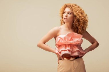 curly redhead woman standing with hands on hips isolated on beige
