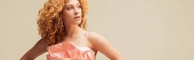 panoramic shot of curly redhead woman looking away isolated on beige