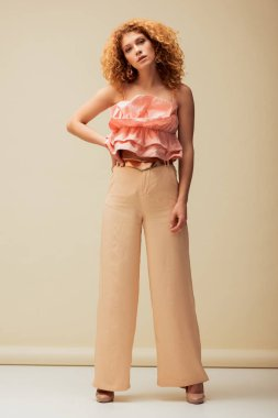 attractive redhead woman standing with hand on hip on beige