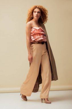 stylish redhead woman in ruffled top and trousers walking on beige