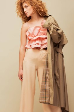 stylish redhead woman in ruffled top and trousers holding trench coat while posing isolated on beige