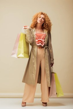 stylish redhead woman in ruffled top, trousers and trench coat holding shopping bags on beige