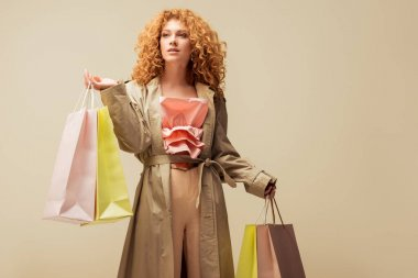 attractive redhead woman in ruffled top and trench coat holding shopping bags isolated on beige