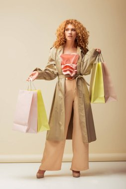 attractive redhead woman in ruffled top, trousers and trench coat holding shopping bags on beige