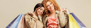 panoramic shot of happy multicultural girls in trench coats holding shopping bags isolated on beige