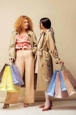 attractive multicultural girls in trench coats holding shopping bags and looking at each other on beige