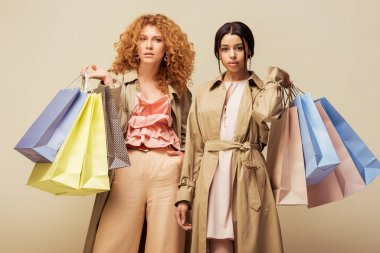 beautiful multicultural girls in trench coats holding shopping bags isolated on beige
