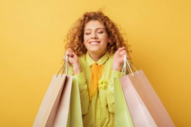 Happy redhead woman with closed eyes holding shopping bags isolated on yellow stock vector