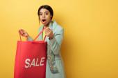 überrascht afrikanisch-amerikanische Mädchen mit Einkaufstasche mit Verkauf Schriftzug auf gelb