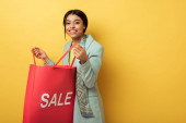 mosolygós afro-amerikai lány gazdaság bevásárló táska eladó felirattal sárga