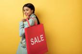 positive afrikanisch-amerikanische Mädchen hält Einkaufstasche mit Verkauf Schriftzug und lächelt auf gelb