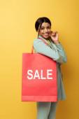 Fotografie positive afrikanisch-amerikanische Frau mit Einkaufstasche mit Verkauf Schriftzug und Lächeln auf gelb