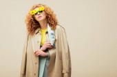 stylová zrzka žena v trenč kabát a sluneční brýle s květy pózovat izolované na béžové