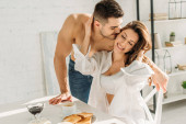 Photo handsome shirtless man kissing smiling girl touching his face while sitting near breakfast
