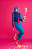 překvapený pop art dívka v fialové paruce a 3D brýle házet popcorn, na růžové