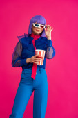 happy pop art girl in purple wig and 3d glasses holding popcorn, isolated on pink