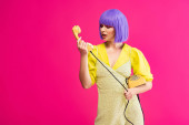 emotional woman in purple wig holding retro telephone, isolated on pink