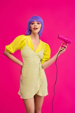 Fashionable pop art girl in purple wig using hair dryer, isolated on pink stock vector