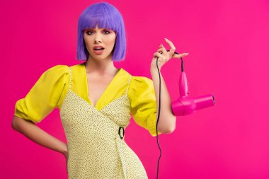 Confused pop art girl in purple wig holding hair dryer, isolated on pink stock vector