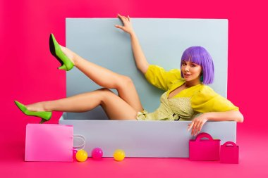 Beautiful emotional girl in purple wig as doll lying in blue box with shopping bags and balls, on pink stock vector
