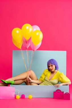 Attractive woman in purple wig as doll holding balloons and sitting in blue box with balls and shopping bags, on pink stock vector