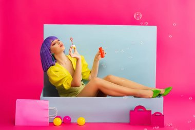 Attractive girl in purple wig as doll blowing soap bubbles while sitting in blue box with balls and shopping bags, on pink stock vector