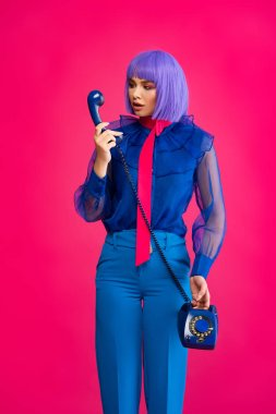 Fashionable girl in purple wig talking on retro telephone, isolated on pink stock vector