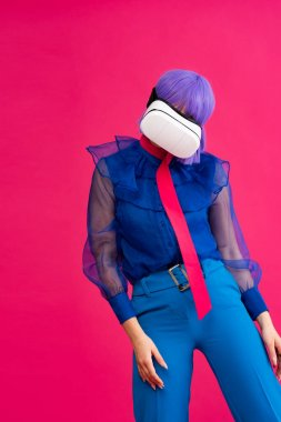 Pop art girl in blue blouse and purple wig using virtual reality headset, isolated on pink stock vector