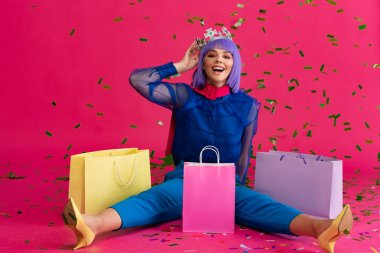 happy girl in purple wig and crown sitting with shopping bags and holiday confetti, on pink