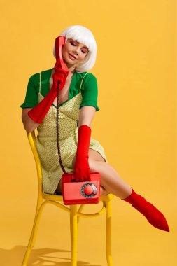 Pop art girl in white wig talking on retro telephone, on yellow stock vector