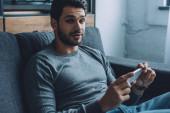 Schöner Mann schaut auf Kamera, während er Pornos auf dem Smartphone auf der Couch anschaut