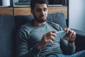 Trauriger Mann schaut Pornos auf Smartphone auf Couch im Wohnzimmer