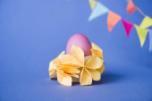 selective focus of origami flowers near easter egg on blue