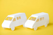 white paper cars on yellow with copy space