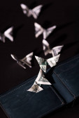 selective focus of money origami butterflies near wallet isolated on black