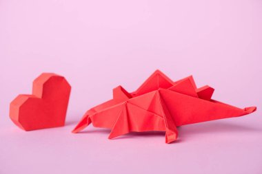 Red paper heart near origami dinosaur on pink stock vector