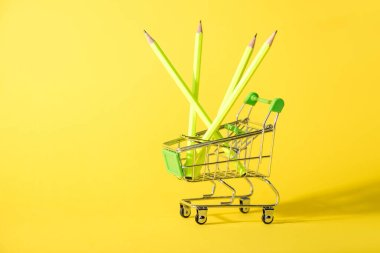 Toy shopping cart with pencils on yellow stock vector