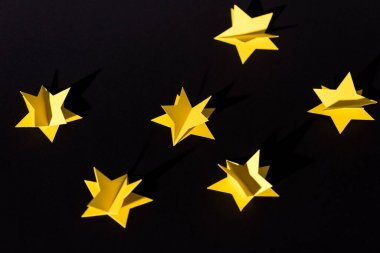 Decorative yellow paper stars isolated on black stock vector
