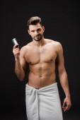 sexy usměvavý muž drží deodorant izolované na černé