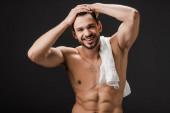 Fotografie schöner lächelnder nackter Mann mit Handtuch isoliert auf schwarz
