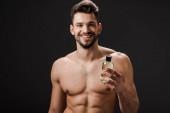 usmívající se nahý muž drží láhev kolínské izolované na černé
