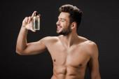 sexy usměvavý nahý muž drží láhev kolínské izolované na černé