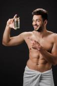 sexy veselý muž ukazuje na láhev kolínské izolované na černé