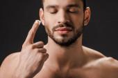 vousatý muž se zavřenýma očima nanášení krému na obličej izolované na černé