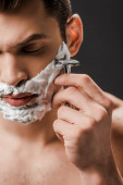 handsome man shaving face with razor isolated on grey